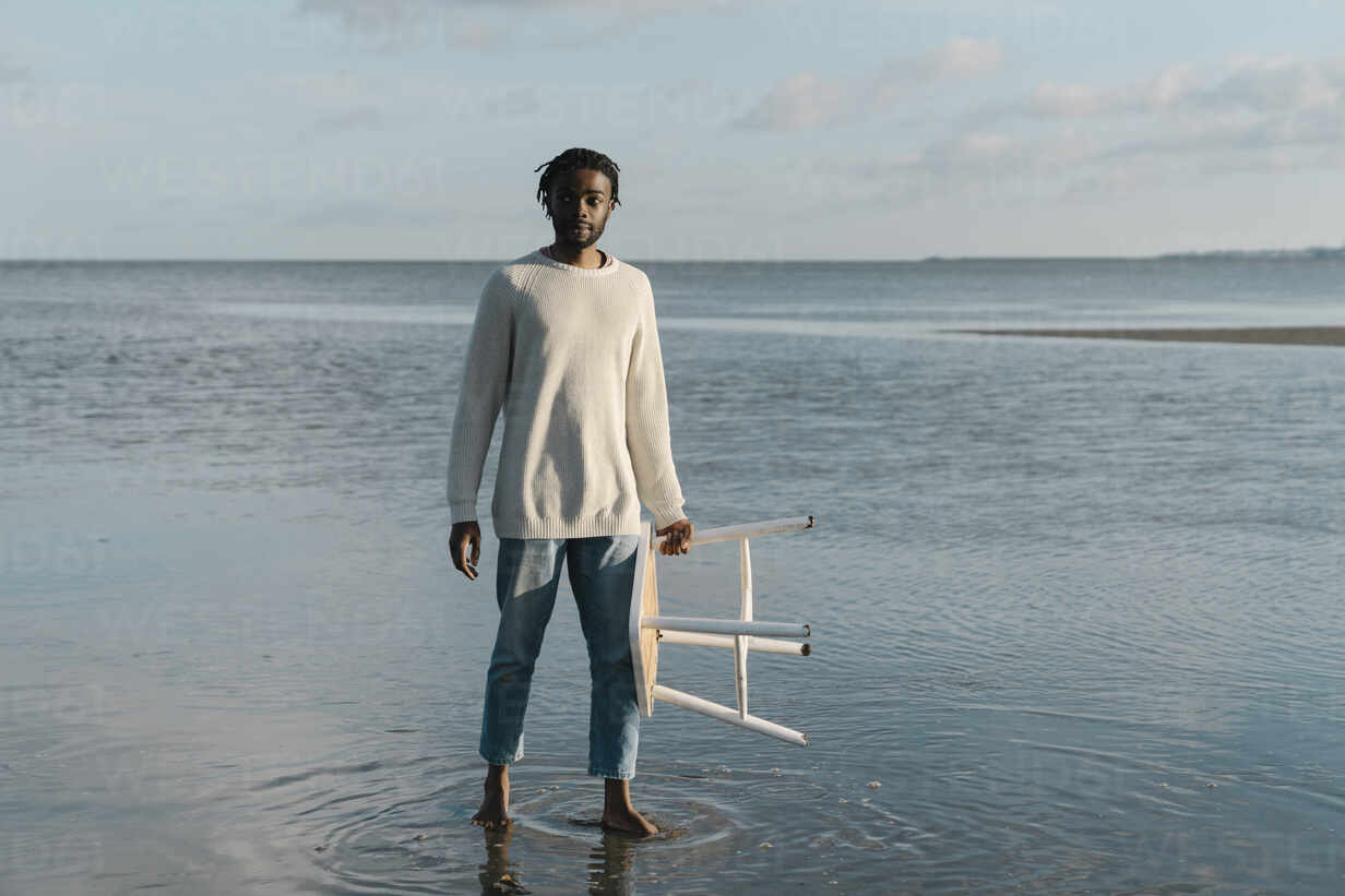 Young man with white stool standing at beach against sky - BOYF01916 - Boy/Westend61