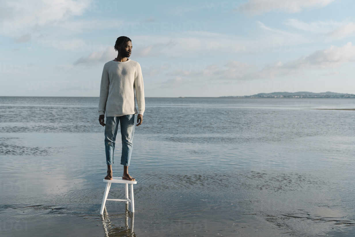 Thoughtful young man looking away while standing on stool at beach during sunset - BOYF01919 - Boy/Westend61