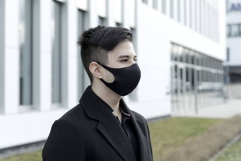 Young male entrepreneur in protective face mask against office building - FLLF00585