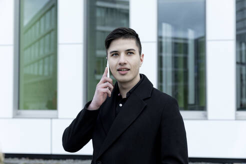 Young male entrepreneur talking on phone while standing against office building - FLLF00588