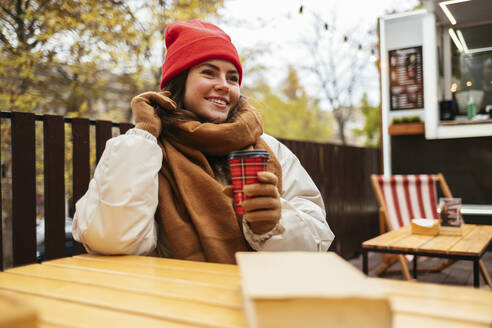 Young woman wearing knit hat and scarf smiling while sitting at sidewalk cafe - OYF00316