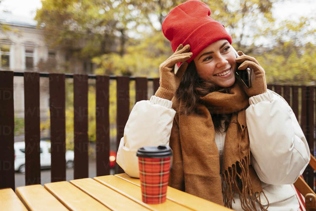 Lächelnde Frau, die wegschaut, während sie auf dem Smartphone sitzt, in einem Straßencafé - OYF00322 - alev/Westend61