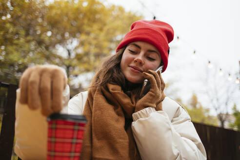 Woman wearing warm clothing talking on smart phone while sitting at sidewalk cafe - OYF00325