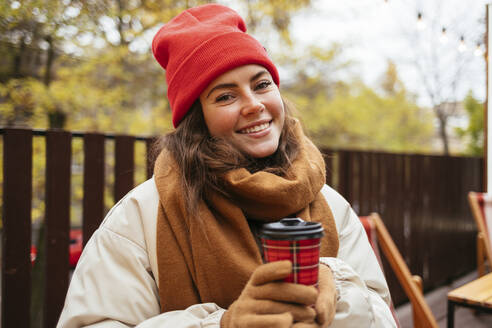 Woman with disposable coffee cup smiling while sitting at sidewalk cafe - OYF00328