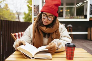 Woman wearing eyeglasses reading book while sitting at sidewalk cafe - OYF00331