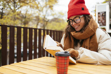 Woman smiling while reading book sitting at sidewalk cafe - OYF00334