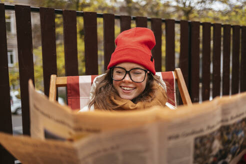 Smiling woman wearing knit hat and eyeglasses reading newspaper while sitting at sidewalk cafe - OYF00340
