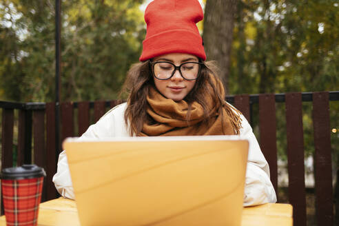 Woman wearing knit hat and scarf using laptop while sitting at sidewalk cafe - OYF00343