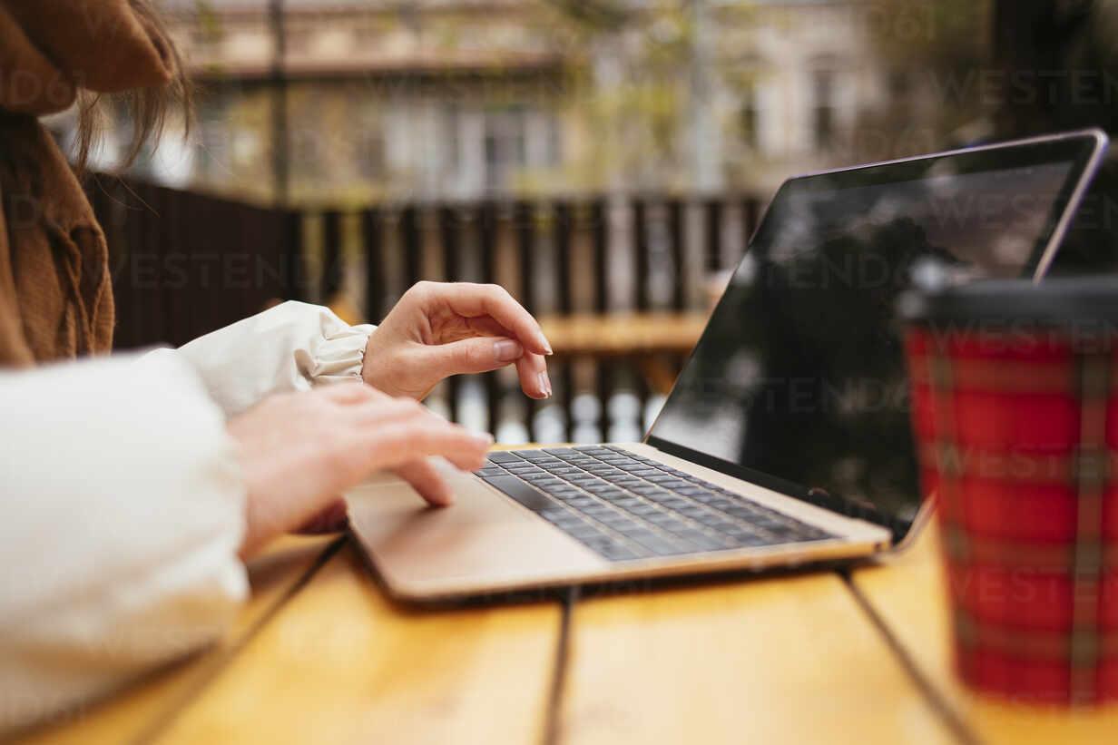 Frau mit Laptop beim Sitzen am Bürgersteig Café - OYF00349 - alev/Westend61