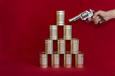 Human hand holding gun against stack of tin cans - DRF01760
