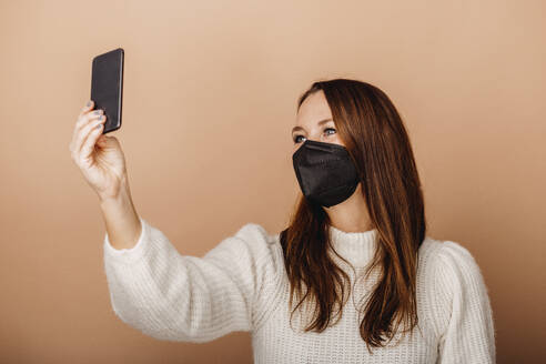 Young woman wearing protective face mask taking selfie through mobile phone while standing against beige background - DAWF01758