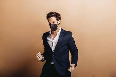 Mann mit FFP2 Maske und beige farbigen Hintergrund. Österreich, Kärnten, Klagenfurt - DAWF01761