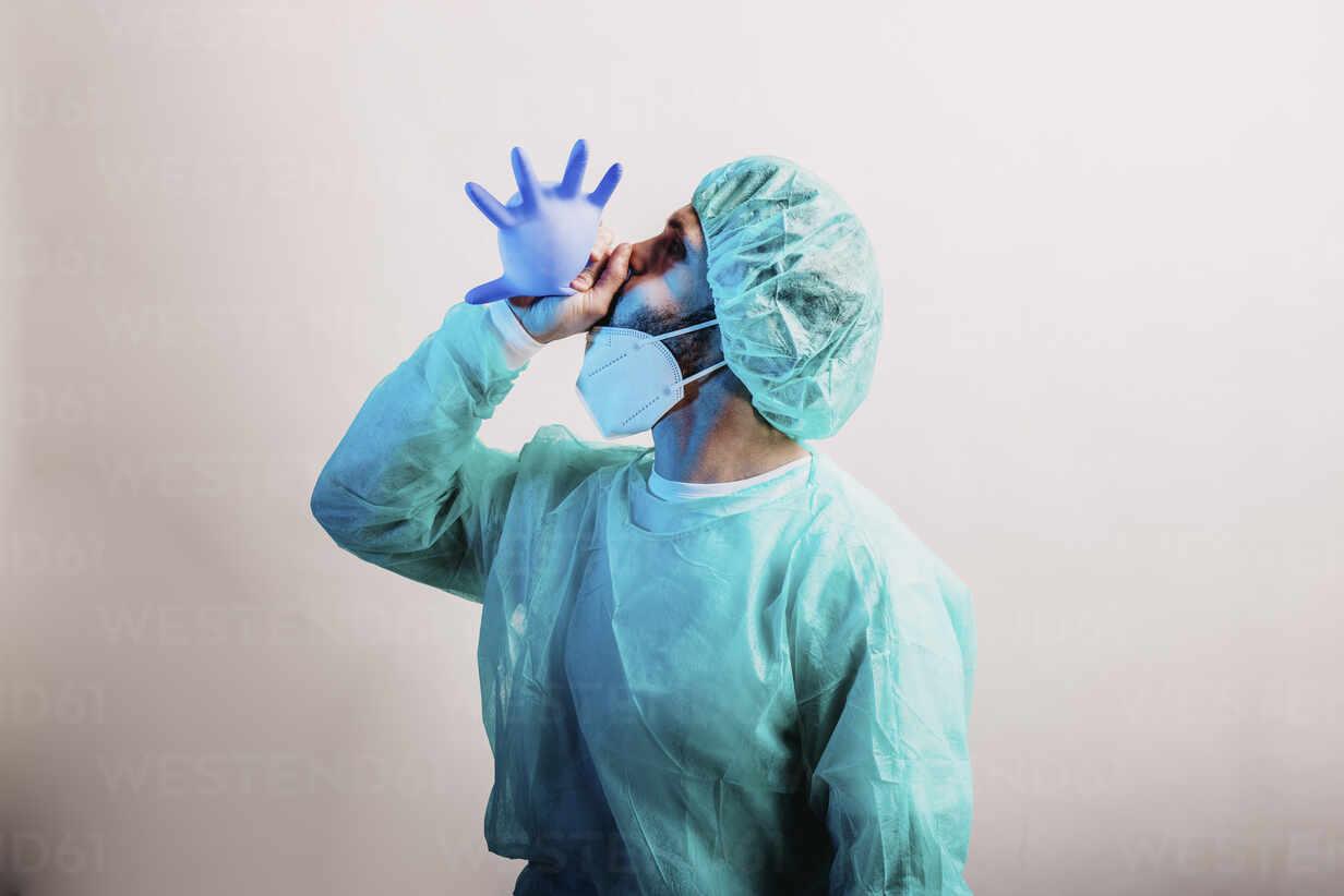 Männlicher Arzt in Schutzanzug bläst chirurgischen Handschuh, während er vor grauem Hintergrund steht - DAWF01764 - Daniel Waschnig Photography/Westend61