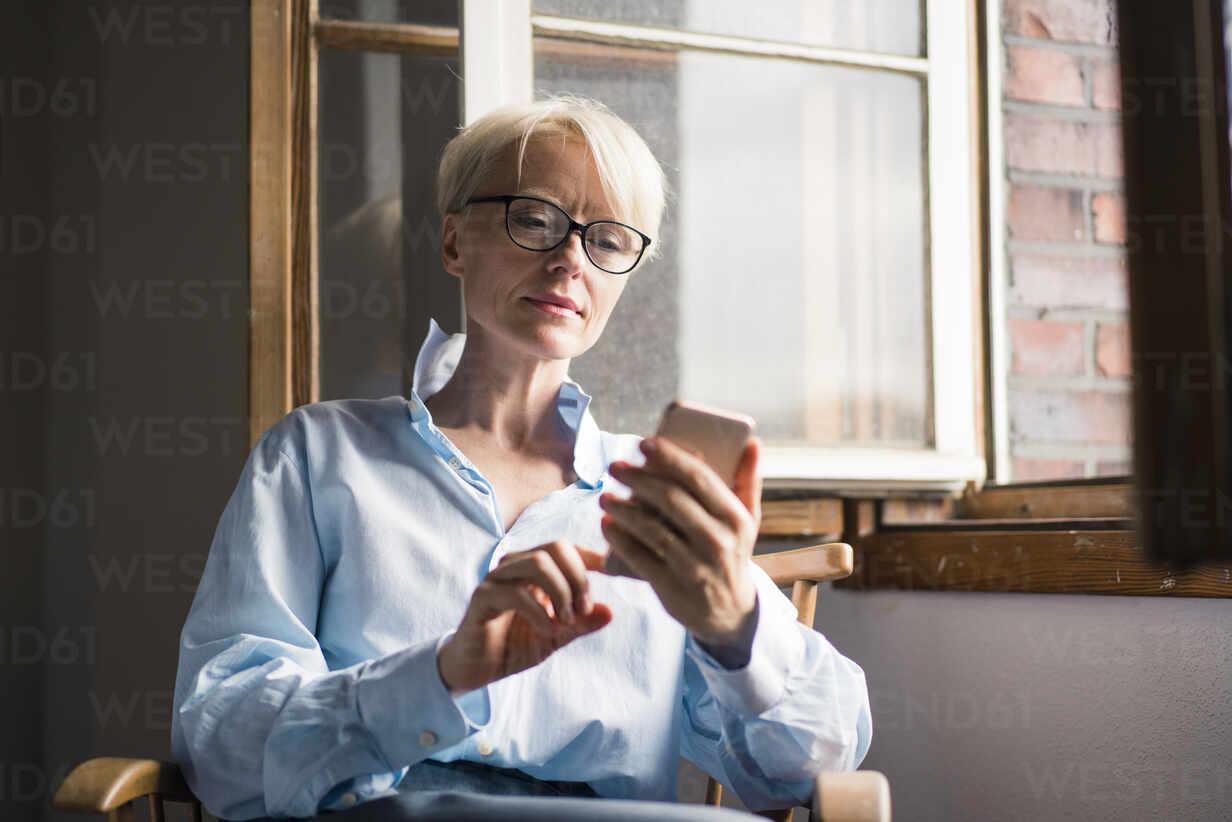 Reife Geschäftsfrau mit Handy während des Sitzens auf Stuhl am Fenster im Büro zu Hause - MOEF03571 - Robijn Page/Westend61