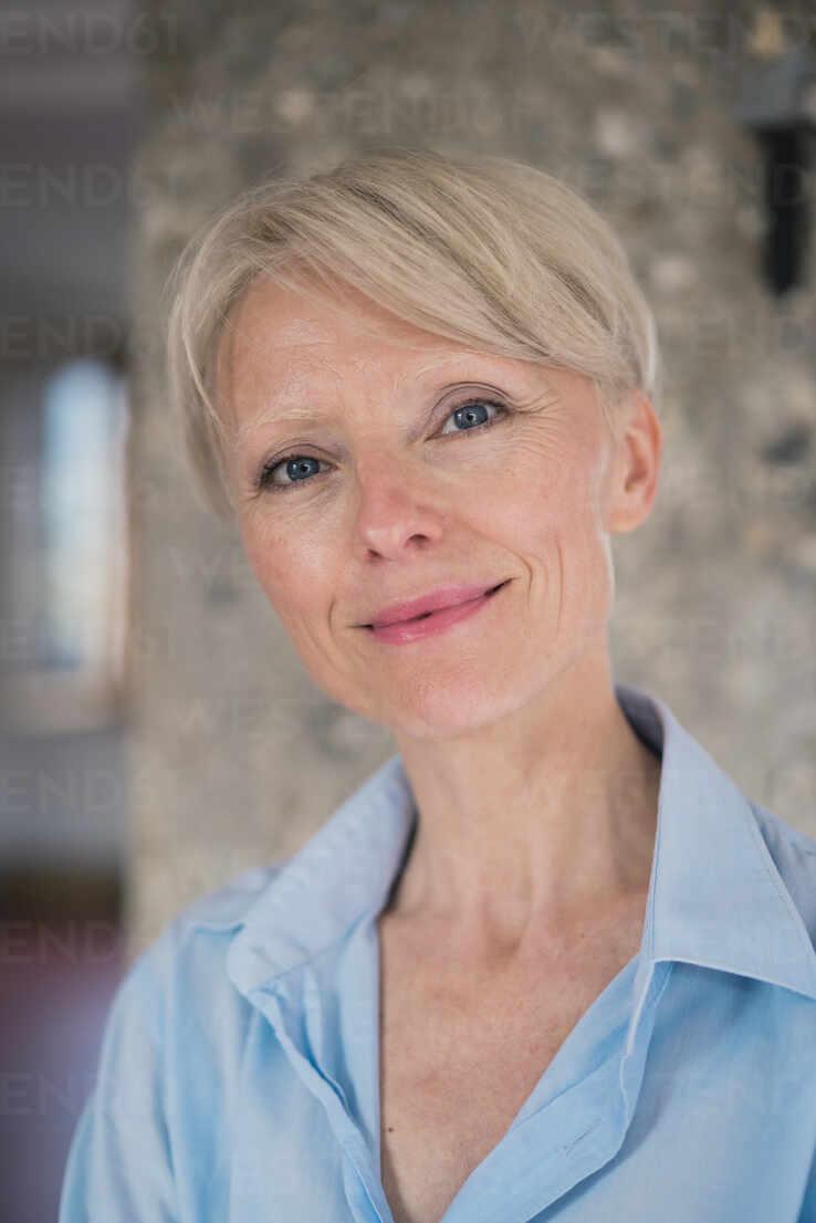 Lächelnde schöne Unternehmerin gegen Säule zu Hause - MOEF03586 - Robijn Page/Westend61