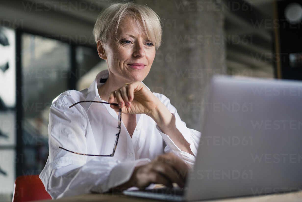 Lächelnde Geschäftsfrau, die eine Brille hält, während sie am Laptop im Büro zu Hause arbeitet - MOEF03598 - Robijn Page/Westend61