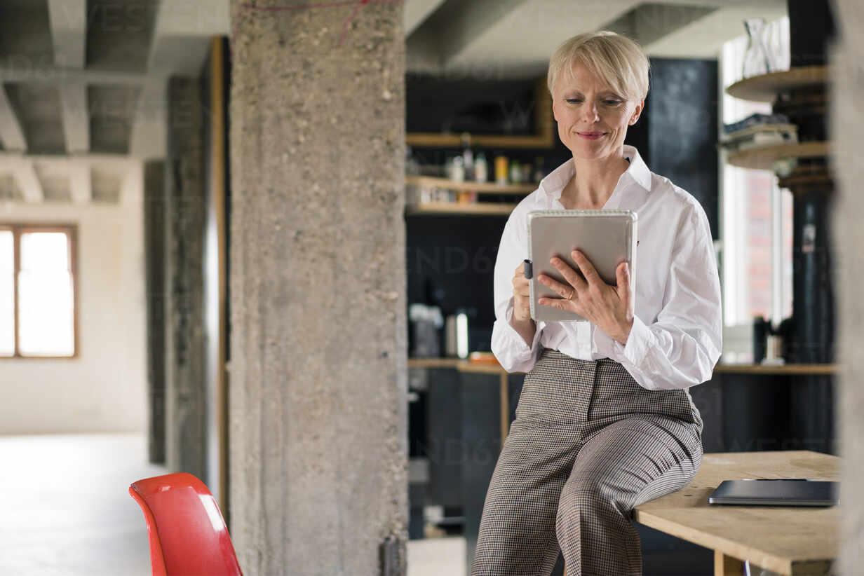 Lächelnde Unternehmerin, die ein digitales Tablet benutzt, während sie auf dem Schreibtisch im Büro zu Hause sitzt - MOEF03601 - Robijn Page/Westend61