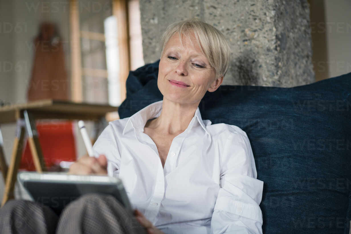 Smiling businesswoman using digital tablet while relaxing on floor chair at home - MOEF03604 - Robijn Page/Westend61