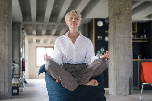 Blond businesswoman meditating while sitting on beanbag at home - MOEF03607