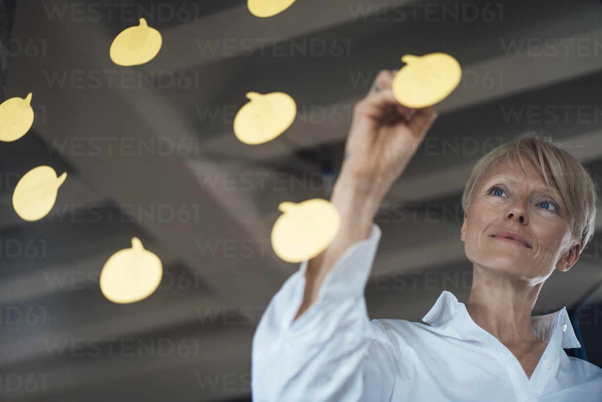 Reife Geschäftsfrau mit blauen Augen, die auf Haftnotizen schreibt, die an einer Glaswand im Heimbüro kleben - MOEF03616 - Robijn Page/Westend61