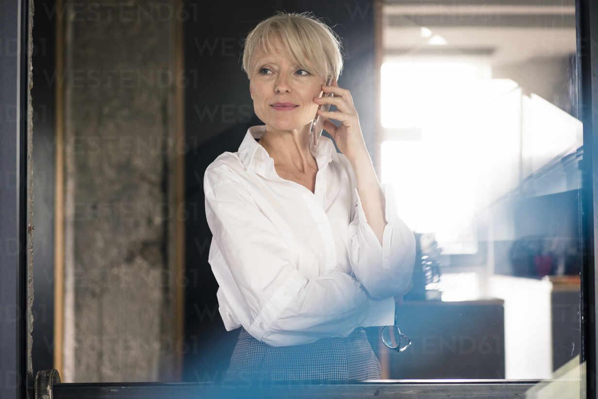 Weibliche Unternehmerin spricht am Handy vor einer Glaswand im Home Office - MOEF03619 - Robijn Page/Westend61