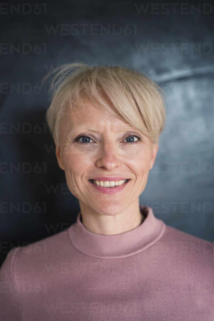 Lächelnde blonde Geschäftsfrau mit blauen Augen gegen die Wand - MOEF03628 - Robijn Page/Westend61