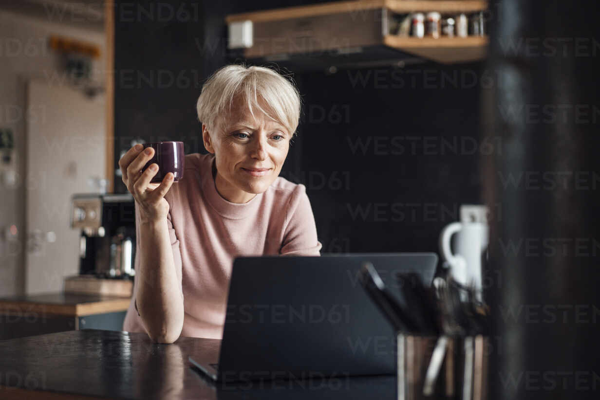 Smiling businesswoman looking at laptop while holding coffee cup at kitchen counter in home office - MOEF03631 - Robijn Page/Westend61