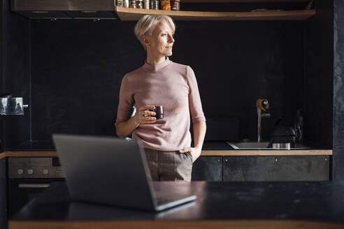 Female entrepreneur with hands in pockets looking away while having coffee in kitchen in home office - MOEF03634