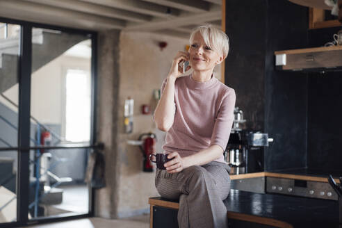 Smiling businesswoman with coffee cup looking away while talking on mobile phone in kitchen at home - MOEF03637