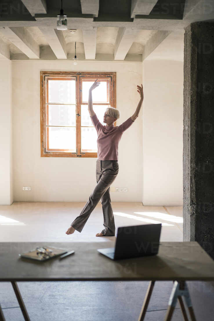 Woman dancing against window in loft apartment - MOEF03640 - Robijn Page/Westend61