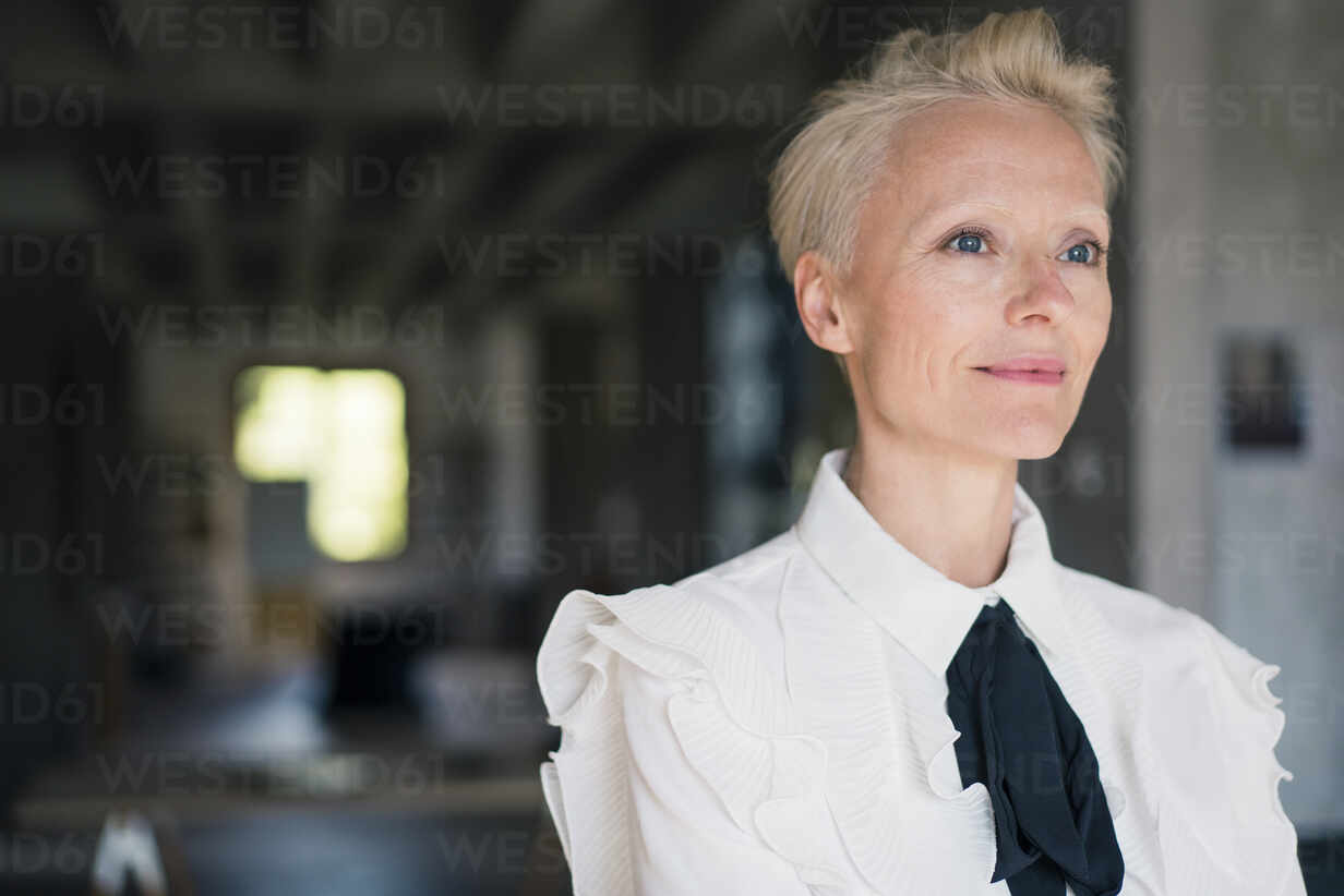 Blond businesswoman day dreaming in loft apartment - MOEF03649 - Robijn Page/Westend61