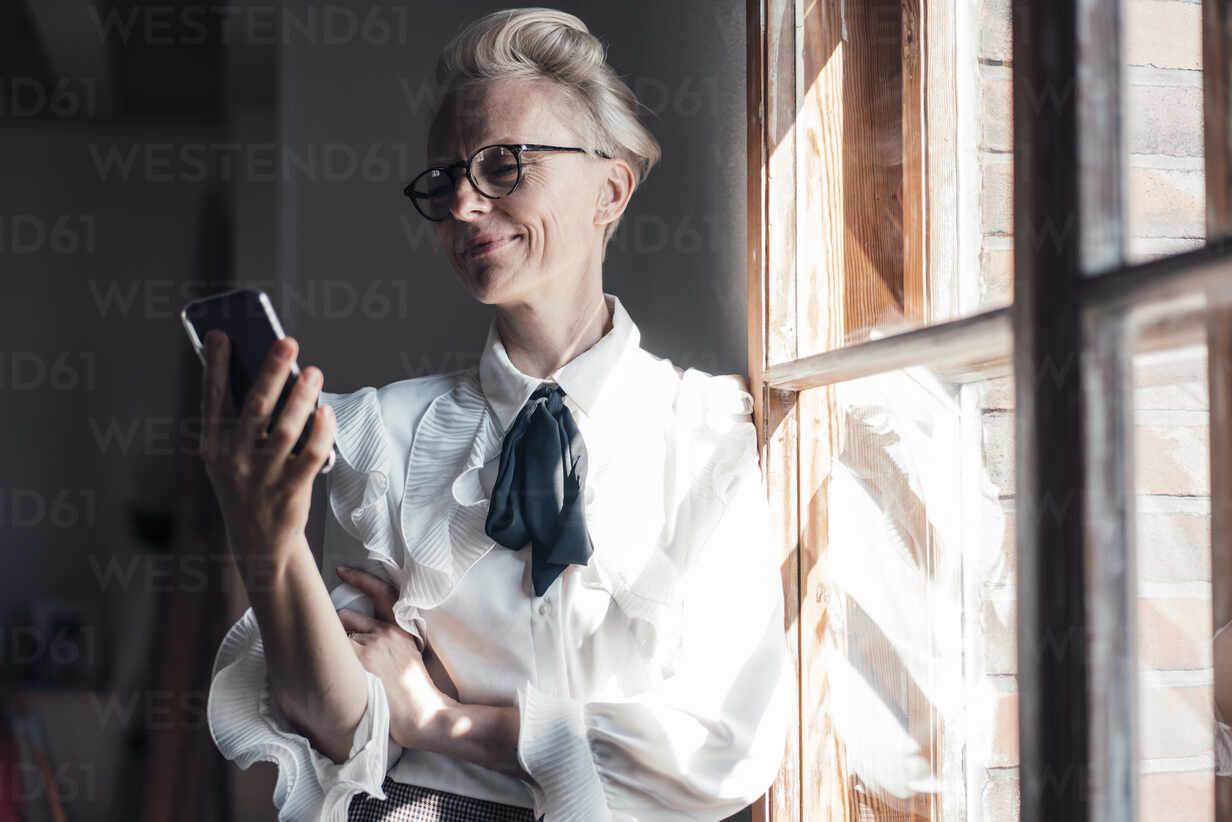 Lächelnde Geschäftsfrau, die auf ihr Handy schaut, während sie am Fenster im Büro zu Hause steht - MOEF03652 - Robijn Page/Westend61