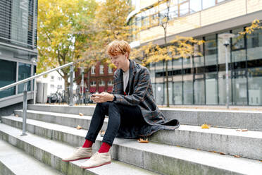 Smiling man using smart phone while sitting on steps against building - OGF00895