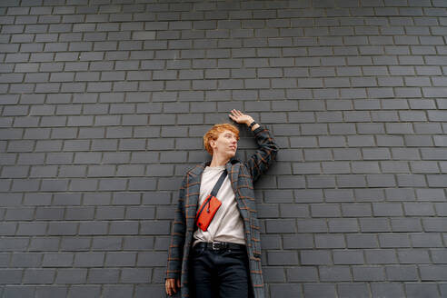 Redhead man with hand raised leaning on wall - OGF00898
