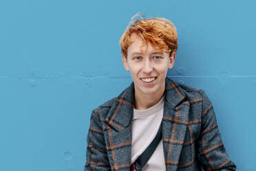 Smiling redhead man against blue wall - OGF00904