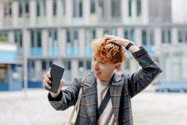 Redhead man with hand in hair taking selfie on smart phone outdoors - OGF00907