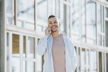 Smiling man talking on mobile phone while standing outdoors - MIMFF00563