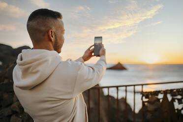 Man taking photo of sunrise over sea through mobile phone while standing on bridge - MIMFF00566