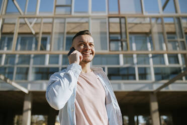 Mid adult man smiling while talking on mobile phone standing against building - MIMFF00575