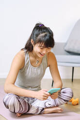 Young woman using mobile phone while sitting on exercise mat at home - AODF00315