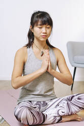 Young woman sitting with hands clasped while practicing yoga at home - AODF00318
