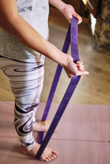 Woman standing on resistance band while exercising at home - AODF00321