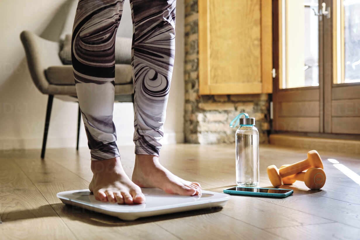 Woman analyzing weight while standing on weight scale at home - AODF00327 - Antonio Ovejero Diaz/Westend61