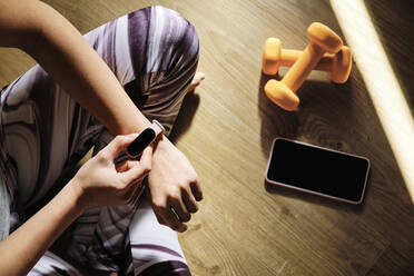 Young woman using smart watch while sitting with cross-legged on floor at home - AODF00330