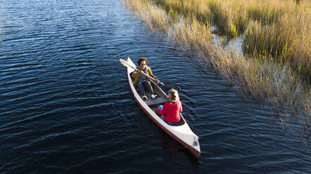 Young couple paddling in canoe in river through grasslands - SBOF02678