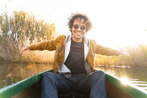 Smiling man sitting with arms outstretched in canoe on river - SBOF02681