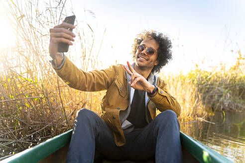 Young man gesturing peace sign while taking selfie through mobile phone sitting in canoe on river - SBOF02684