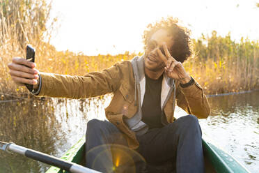 Young man showing peace sign while taking selfie through mobile phone sitting in canoe on river - SBOF02687