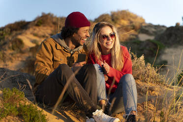 Smiling couple sitting together in dunes on beach with smartphone - SBOF02690
