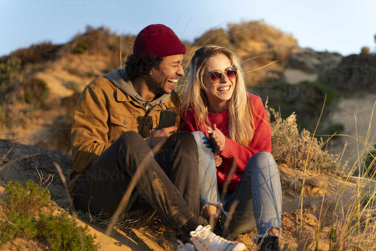 Smiling couple sitting together in dunes on beach with smartphone - SBOF02690 - Steve Brookland/Westend61